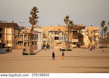 July 25, 2020 In Seal Beach, Ca:  People Walking On The Sandy Beach Surrounded By Palm Trees And Vac