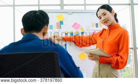 Young Woman Explains Business Data On White Board In Casual Office Room . The Confident Asian Busine