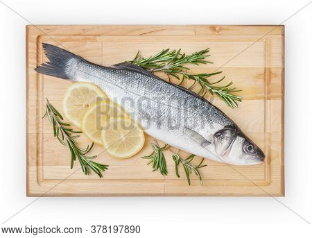 Fresh Uncooked Seabass With Lemon And Rosemary On Wooden Board Over White Backdground With Clipping