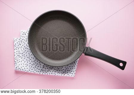 Kitchenware. Frying Pan With A Towel On A Pink Background, Top View.