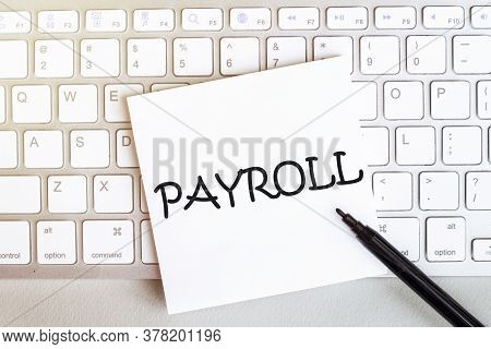 Piece Of Paper With Text Payroll On The Keyboard On A White Background With A Black Felt-tip Pen