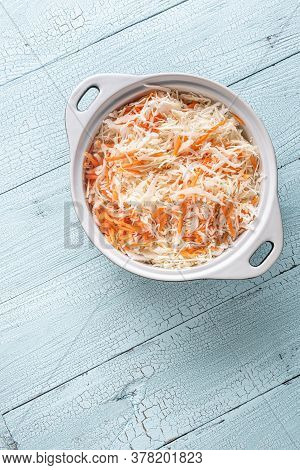 White Ceramic Pan Full Of Grated Cabbage And Carrot On Old Wooden Blue Table. Cooking Stage For Cole