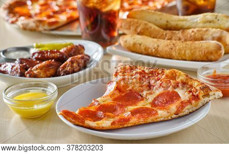 sliced of pepperoni pizza on plate with breadsticks, soft drink and chicken wings in background
