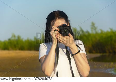 A Beautiful Brunette Holds A Slr Camera In Her Hands And Looks Into The Lens. Photographs On A Summe