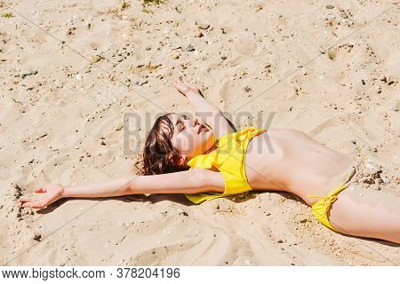 Young Woman Lies In Summer On The Beach. The Girl Lies On The Sand On The Beach. Teenager At Sea. Va