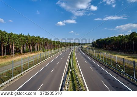 A Two-lane Asphalt Expressway Crossing The Forest In Poland