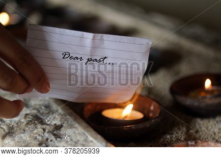 Hand Holding A White Note Paper Written - Dear Past. Burning It On A Burning Candle In A Ceramic Bow