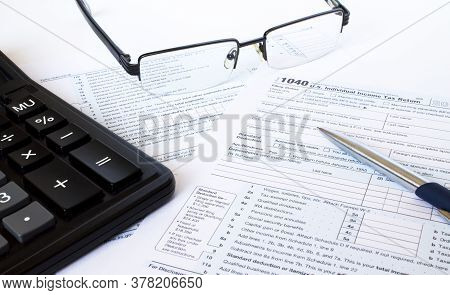 Us Tax Form 1040 With A Silver Pen, Glasses And Calculator