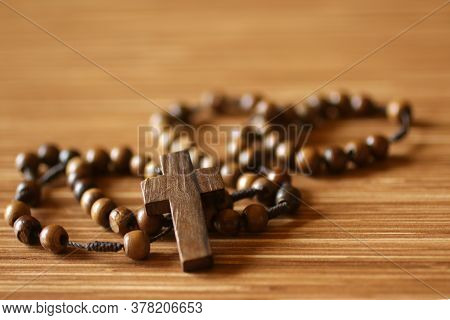 The Rosary. Close Up Of Wooden Rosary Beads With Jesus Christ Holy Cross Crucifix On The Table In Br