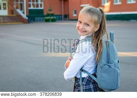 Happy Smiling Girl Go To Elementary School. Child With Grey Backpack, Green Book And In Uniform Is G