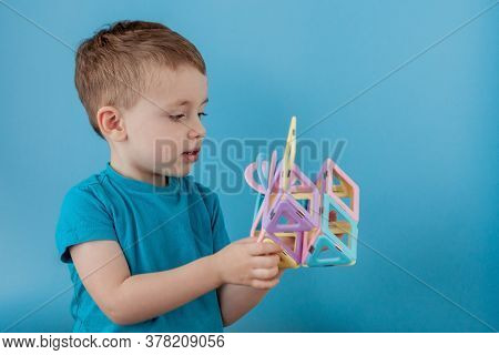 Boy Looks Through The Shape In The Color Constructor With The Connection Of The Magnets