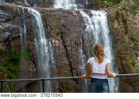 A Girl Stands In Front Of A Waterfall And Admires The Beautiful View Of Falling Water. Blond Woman O