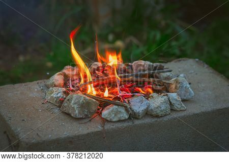Small Burning Fire On A Stone Slab. Concept Of Tourism, Camping, Gatherings Around The Campfire At N