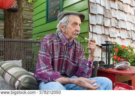 Carthage - Usa September 7 2015; Senior Man Sitting Outside Home In Morning Light Unshaven Smoking P