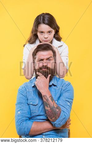 Father Is Idol Of Each Child. Little Daughter Hug Serious Father. Small Girl And Father Yellow Backg