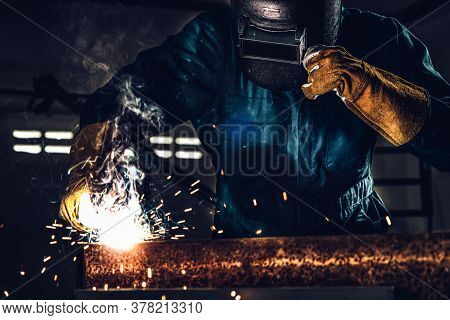 Metal Welder Working With Arc Welding Machine To Weld Steel At Factory While Wearing Safety Equipmen