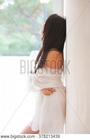 lonely woman near a glass during a pandemic