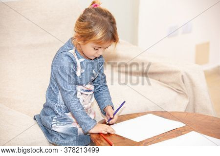 girl drawing on a wooden table isolation during a pandemic