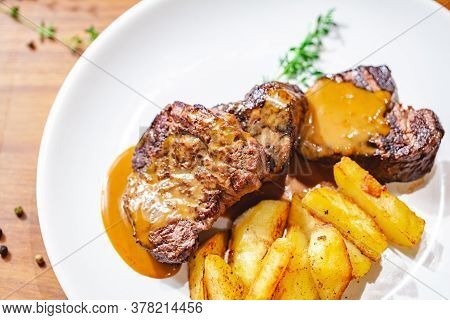 Grilled Beef Steak With Potato Wedges On White Plate. Close Up
