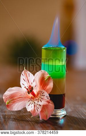 Multi-layered Burning Cocktail Decorated With Flowers On Wooden Table. Close Up