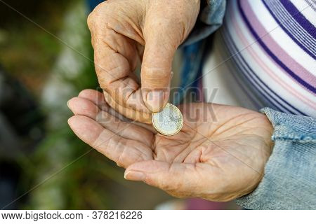 Coin In The Hand Of The Old Lady. An Elderly Woman With One Euro In Her Hands.