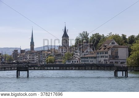 Zurich, Switzerland - 1 August, 2019: Cityscape Of Zurich And River Limmat In Daytime With Blue Sky
