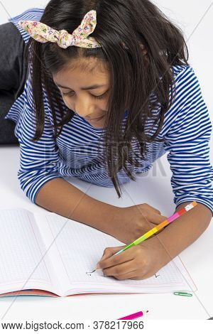 Cute Left-handed Girl Is Writing With A Pencil In Her Notebook.