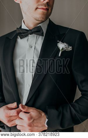 Groom In Wedding Black Tuxedo Smiling And Waiting For Bride In The Hall Of The Hotel . Elegant Groom