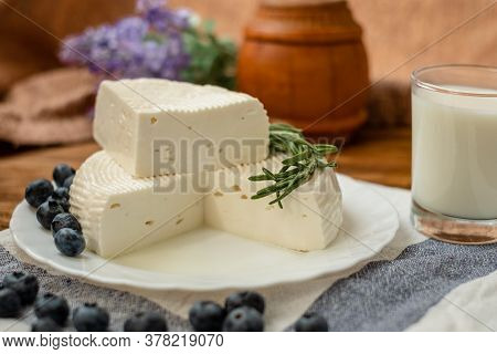 A Head Of Cheese In A White Plate Lies On The Table With Blueberries And Rosemary. Fresh Goat Cheese