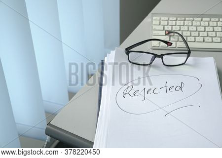 Handwritten Word, Rejected On Top Of Pile Of Documents On Table