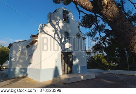 White Chapel Ermita De Sant Vicent Sunlit With Shadows From Big Old Tree In La Nucia, Costa Blanca,