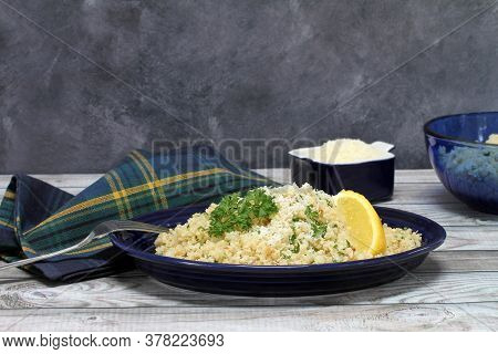 Cauliflower Rice Sprinkled With Parmesan And Garnished With Parsley And A Wedge Of Lemon.  Table Set