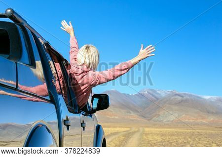 Happy Woman Goes To Summer Or Autumn Travel Trip In The Car. Travel Vacations Concept With Copy Spac