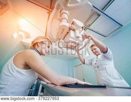 Radiologist And Patient In A X-ray Room. Classic Ceiling-mounted X-ray System.