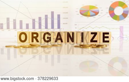 Organize The Word On Wooden Cubes, Cubes Stand On A Reflective Surface, In The Background Is A Busin