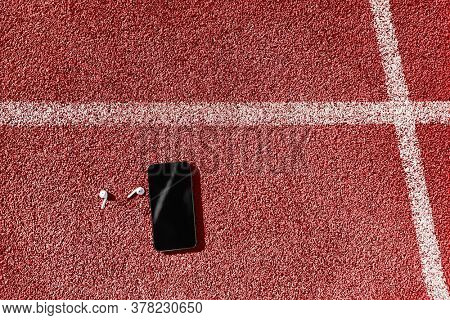 Wireless earbuds lying on red running tracks of athletics stadium. Top view of mobile phone and earphones background for fitness athlete concept.