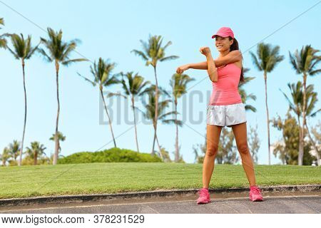 Fitness run woman doing stretch exercise stretching her arms - tricep and shoulders stretch outdoor sports. Fit runner girl living an active lifestyle.
