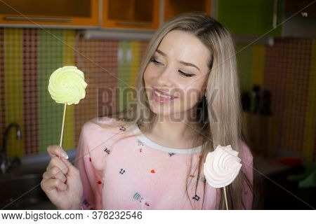 A Young Woman In Pink Pajamas Holds A Sweet Dessert In Her Hands.