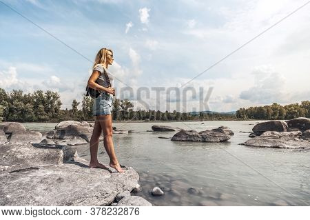 A Tourist With A Backpack On His Back Is Standing Near The River And Looking At The Mountains In The