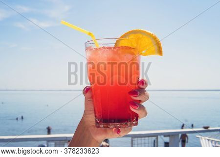 Hand With Orange Coctail Glass Over Turquoise Lagoon Exotic Bay. Lifestyle Summertime Vacation Conce