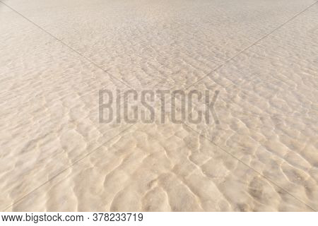 Waves On A Yellow Sandy Bottom Intersect With Waves On The Surface Of The Water. The Texture Of Sand