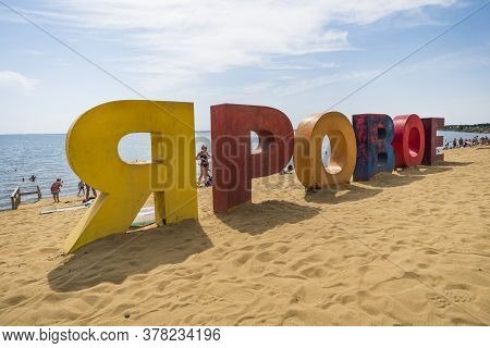 Multicolored Inscription Yarovoe In Russian Language On The Yellow Sand On The Background Of The Lak