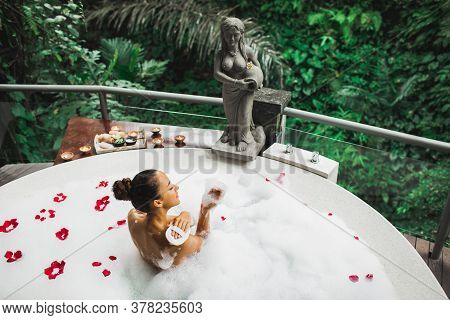 Happy Woman Playing With Foam In Big Bath Tub With Bubbles And Rose Flowers Petals. Relaxation In Sp