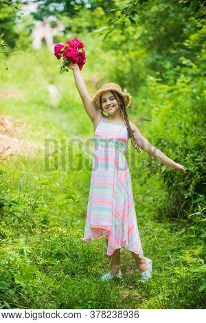 New Flowers. Stunning Girl With Bouquet Flowers Of Roses. Happy Child In Straw Hat. Hairstyle Of Nat