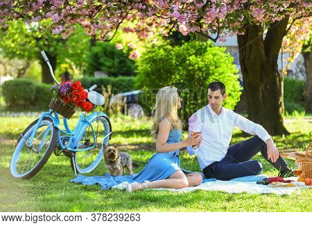 Attractive Couple Enjoying Romantic Sunset Picnic In Countryside. Romance Concept. Inspiring Feeling