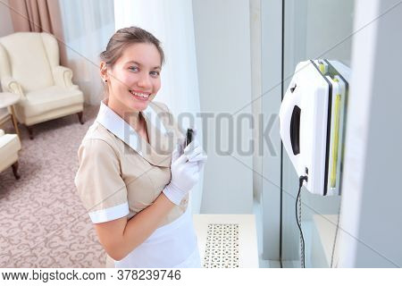A Young Smiling Maid In Uniform Remotely Controls A Robot That Cleans Windows. Cleaning At The Hotel