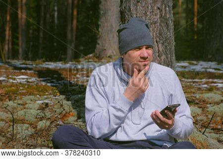 Portrait Of Man Tourist Traveller Watching Map On Smartphone Sitting In Forest. Young Guy Is Travell