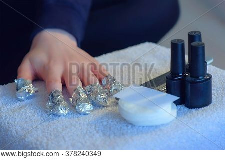 Woman Wrapping Foil With Remover On Nails To Remove Shellac Making Manicure Herself At Home. Removin