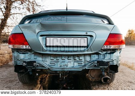 A Car Without A Bumper, The Exhaust Pipe Is Visible. The Trunk Lid Is Dented. Auto After Accident. R