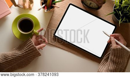 Female Hand Using Tablet With Clipping Path And Holding Coffee Cup On Office Desk